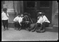 Boys playing checkers on a stoop, probably the Lower East Side, New York City, undated (ca. 1915).