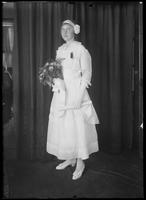 Full-length studio portrait of a young woman in white, holding a bouquet and a rolled document [diploma?], [New York City?], ca. June 1915.