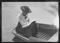 Ethel Magaw Hassler in a rowboat on an unidentified lake, reading, undated (ca. 1915).