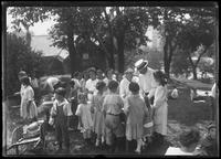 Children and unidentified man at a cookout in a park, New York City, undated (ca. 1915).