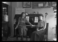 Two unidentified young women posed beside an electric piano with multiple 'Electrical Prosperity Week' posters in the background, New York City, undated (ca. November-December 1915).