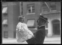 Unidentified man holding an infant, New York City, July 16, 1916.
