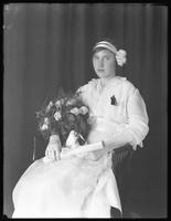 Seated studio portrait of a young woman in white, holding a bouquet and a rolled document [diploma?], [New York City?], ca. June 1915. Motion blur.