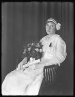 Seated studio portrait of a young woman in white, holding a bouquet and a rolled document [diploma?], [New York City?], ca. June 1915.