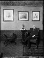 Older man seated beside a trophy in a club-like room, undated [ca. November 1915].