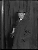 Studio portrait of unidentified man in coat and hat, holding a wrapped parcel, undated [ca, December 1915].