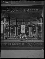 Display of electric irons in the window of Liggett's Drug Store, Broadway and 34th Street, New York City, May 5, 1916. Photographed for the Hot Point Electric Company.