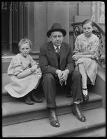 Unidentified man and two girls seated on a stoop on E. 137th Street, [Bronx? New York City?], May 30, 1916.