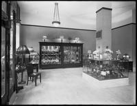 Interior view of the United Electric Light & Power Company shop showroom at W. 89th Street and Broadway, featuring lamps, electrical appliances, and serving ware, New York City, June 5, 1916.