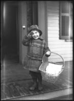 Unidentified child on a porch with an empty basket, saluting, undated [ca. February 1919].
