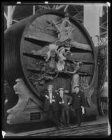 Three unidentified men posed in front of an elaborately carved champagne vat, undated (ca. 1910-1922).