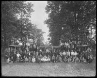 Unidentified large group portrait with trucks and American flags, undated (ca. 1911-1922).