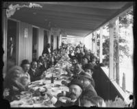 Large group of unidentified men seated at a long table on a porch, undated (ca. 1911-1922).