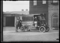 Motorized Bellevue Hospital ambulance, with unidentified driver, passenger, and onlooker, New York City, undated (ca. 1911-1922).