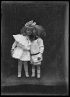 Studio portrait of two small children in white, one kissing the other, undated (ca. 1911-1922).