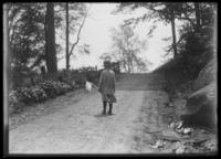 William Gray Hassler walking along a dirt road with fishing rod and net, probably New York City, undated (ca. 1912-1915).