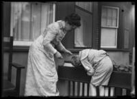 William Gray Hassler and Harriet E. Hassler looking at plants in a flowerbox, Queens (?), undated (ca. 1913-1915).