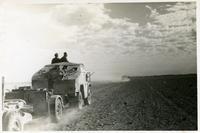 An armored vehicles with soldiers and a cannon photographed on a stone desert