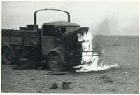 A burning on a desert military truck