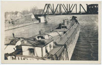 Laden barge with woman at tiller passing under railroad truss bridge (1front) [c0061ac1]