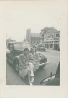 Two Women seated on bumper of car on Hamilton Avenue
