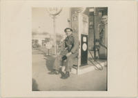 Man in coveralls seated at gas pump