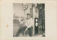 Young Man seated at gas pump